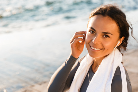 Photo of young fitness woman outdoors on the beach have a rest sitting with towel looking camera listening music with earphones.