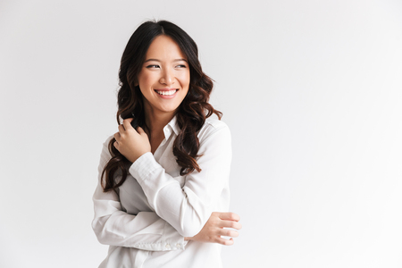 Photo of optimistic asian woman with long dark hair looking aside at copyspace and laughing isolated over white background in studio
