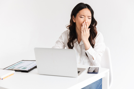 Photo of overworked tired asian business woman 20s wearing office clothing yawning while sitting at table with laptop open isolated over white background