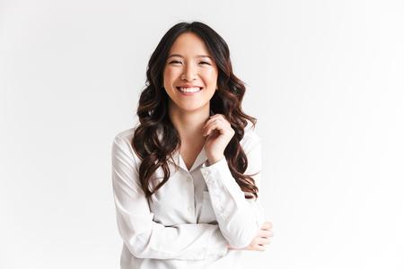Retrato de hermosa mujer asiática con cabello largo y oscuro riéndose de la cámara con hermosa sonrisa aislada sobre fondo blanco en estudio