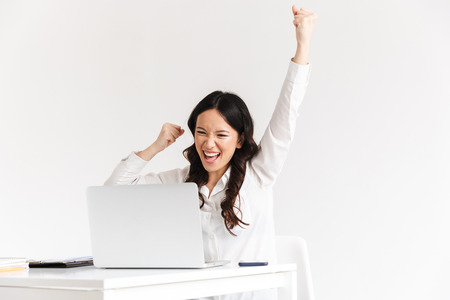 Photo of happy chinese businesswoman with long dark hair screaming with raised arms while working with documents and laptop isolated over white background
