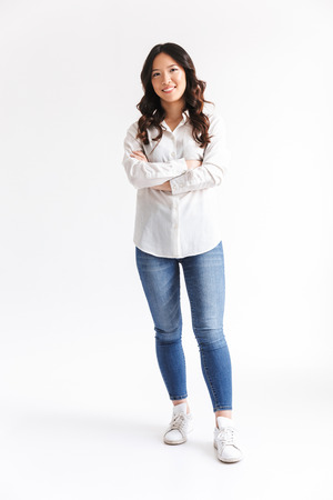 Full length photo of happy asian woman with long dark hair looking at camera with beautiful smile and arms crossed isolated over white background in studio Stock Photo