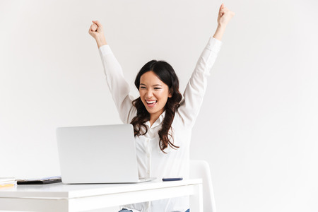 Photo of excited chinese businesswoman with long dark hair screaming with raised arms and celebrating success while working in office isolated over white background