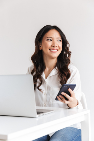 Smiling young asian businesswoman holding mobile phone while sitting with laptop computer over white background