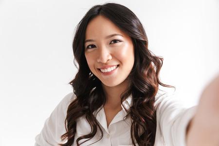 Ritratto di donna cinese felice con capelli scuri lunghi che sorride alla macchina fotografica e che prende la foto del selfie isolata sopra fondo bianco in studio