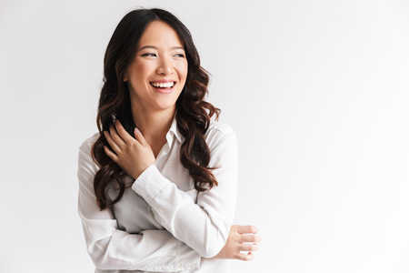 Image of charming chinese woman with long dark hair looking aside at copyspace and laughing isolated over white background in studio