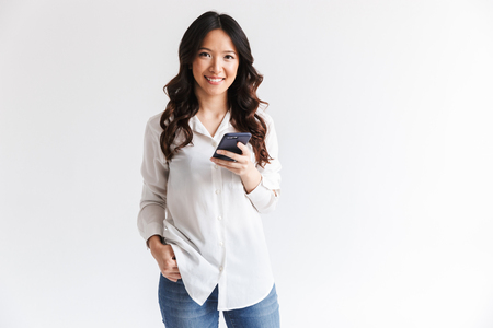 Photo of smiling charming asian woman with long dark hair holding black cell phone isolated over white background in studio