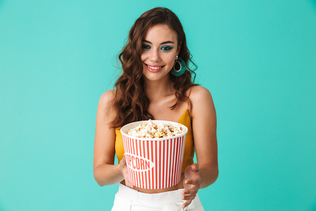 Photo of glamorous brunette woman 20s wearing fashion earrings holding bucket with popcorn and looking at camera isolated over blue background Stock Photo