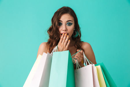 Photo of trendy young girl 20s wearing fashion style holding colorful paper shopping bags with purchases isolated over blue background