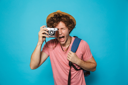 Photo of happy traveler man 18-20 with curly hair wearing backpack and straw hat photographing on retro camera, isolated over blue background