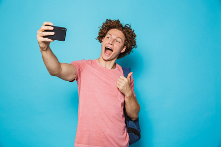 Photo of handsome college guy with curly hair wearing casual clothing and backpack holding smartphone and taking selfie isolated over blue background Stock Photo