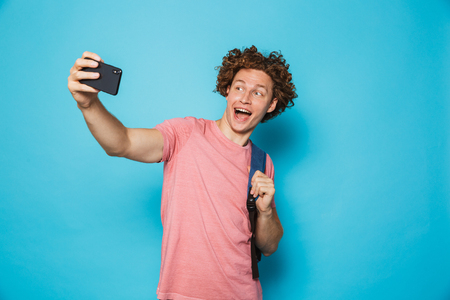 Image of positive youngster guy with curly hair wearing casual clothing and backpack holding smartphone and taking selfie isolated over blue background