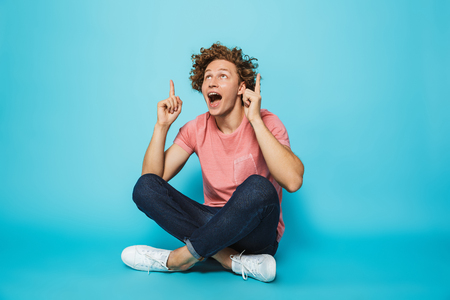 Portrait of a happy young curly haired man pointing up while sitting with legs crossed over blue background