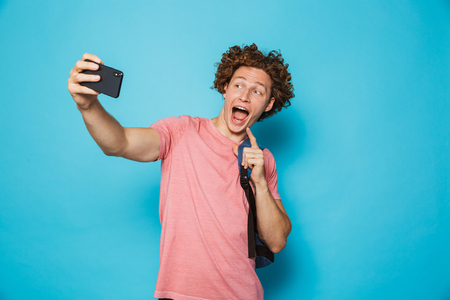 Image of caucasian youngster guy with curly hair wearing casual clothing and backpack holding smartphone and taking selfie isolated over blue background