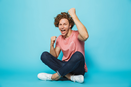 Portrait of a cheerful young curly haired man celebrating while sitting with legs crossed over blue background 스톡 콘텐츠