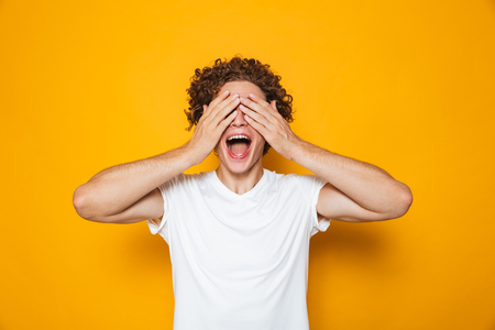 Young happy man 20s with brown curly hair screaming and covering eyes with hands isolated over yellow background