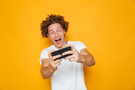 Cheerful excited guy in casual t-shirt playing online video games using mobile phone isolated over yellow background