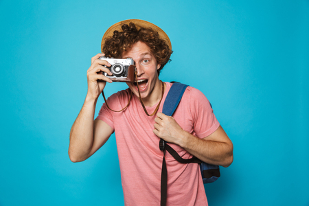 Image of attractive tourist man 18-20 with curly hair wearing backpack and straw hat photographing on retro camera isolated over blue background