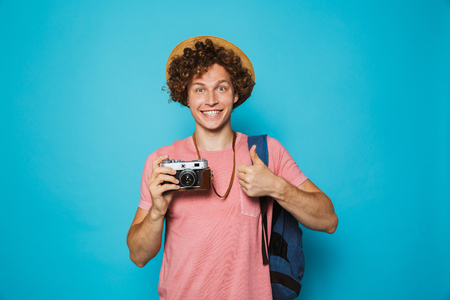 Photo of caucasian young man 18-20 with curly hair wearing backpack and straw hat photographing on retro camera isolated over blue background