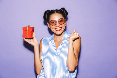 Portrait of a delighted young woman in sunglasses isolated, holding present box