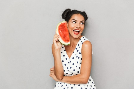 Portrait of a joyful young woman in summer dress isolated, holding watermelon slice