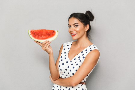 Portrait of an attractive young woman in summer dress isolated, holding watermelon slice 写真素材