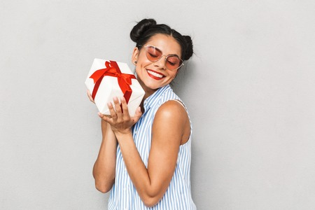 Portrait of a satisfied young woman in sunglasses isolated, holding present box