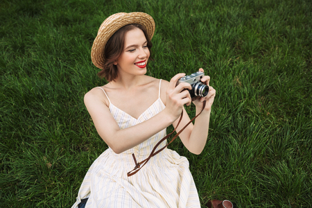 Happy woman in dress and straw hat making photo on retro camera while sitting on grass outdoors