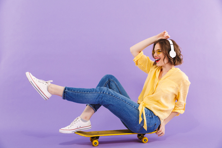 Portrait of a happy young girl in headphones sitting on skateboard isolated over violet background Stockfoto