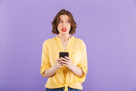 Photo of confused young woman isolated over purple wall background using mobile phone. 版權商用圖片