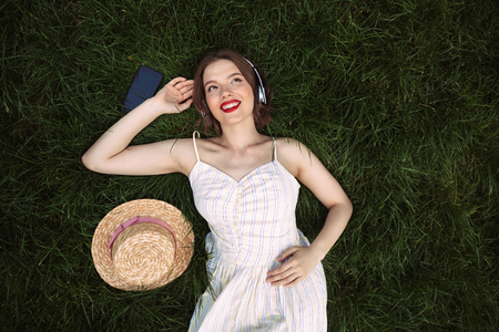 Top view of happy woman in dress and headphones lying on grass while listening music and looking away outdoors Stok Fotoğraf