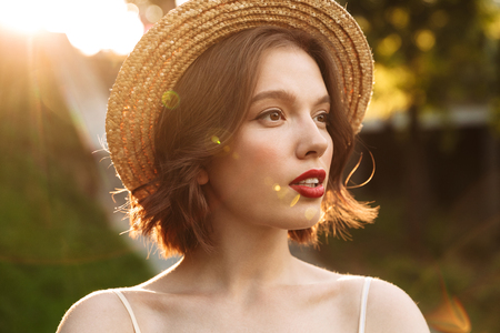 Close up picture of young pretty woman in dress and straw hat looking away while posing outdoors