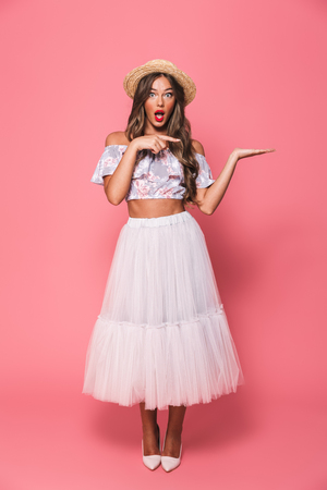 Full length portrait of lovely surprising woman 20s wearing straw hat and fluffy skirt holding copyspace on palm and pointing finger aside isolated over pink background