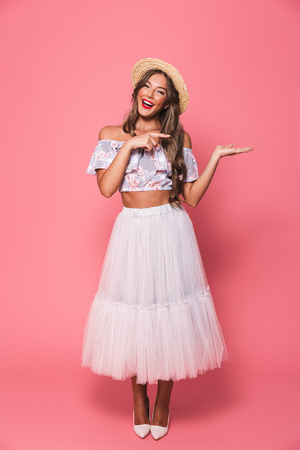 Full length portrait of excited pretty woman 20s wearing straw hat and fluffy skirt holding copyspace on palm and pointing finger aside isolated over pink background