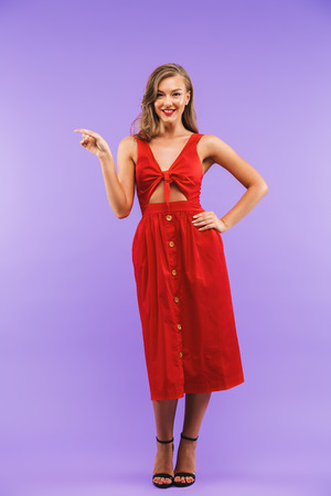 Full length portrait of gorgeous brunette woman 20s wearing red dress smiling and pointing finger aside at copyspace standing isolated over violet background