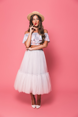 Full length portrait of brunette surprised woman 20s wearing straw hat and fluffy skirt thinking and touching chin with brooding glance isolated over pink background