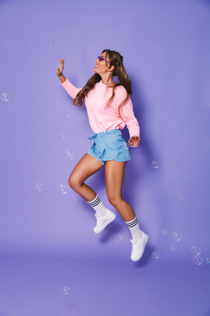 Full length portrait of funny teenage woman with two ponytails in sweatshirt smiling and jumping isolated over violet background in studio Stock Photo