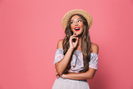 Portrait of pretty glamour woman 20s wearing straw hat laughing and looking aside isolated over pink background in studio