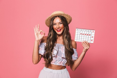 Portrait of a happyyoung girl in summer clothes showing periods calendar over pink background, showing ok