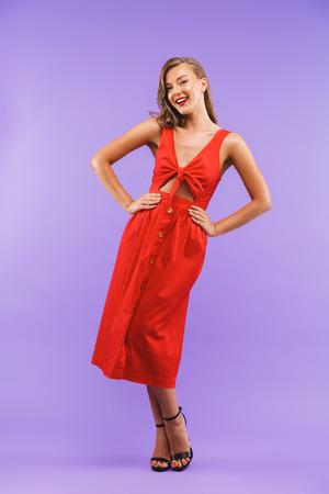 Porträt in voller Länge der kaukasischen niedlichen Frau 20s, die rotes Kleid lächelnd an der Kamera steht, die über violettem Hintergrund steht Standard-Bild