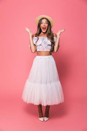 Full length portrait of brunette surprised woman 20s wearing straw hat and fluffy skirt screaming while raising hands isolated over pink background in studio Stock Photo