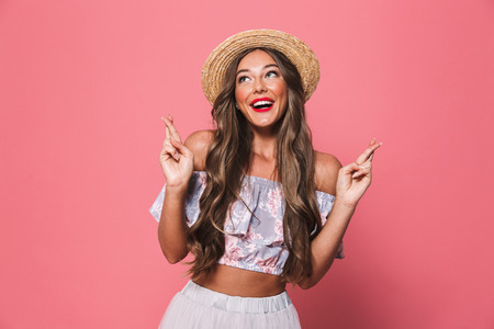 Image of charming young lady in straw hat holding fingers crossed and praying or dreaming for good luck isolated over pink background Stok Fotoğraf