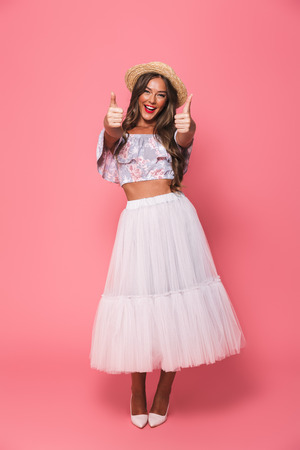 Full length portrait of beautiful excited woman 20s wearing straw hat and fluffy skirt showing thumbs up isolated over pink background in studio