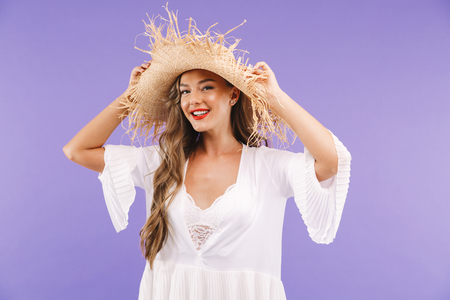 Portrait of a smiling young woman in white dress and straw hat posing while standing isolated