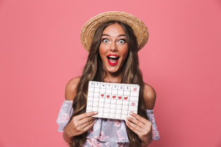 Photo of attractive glamour woman 20s wearing straw hat holding menses calendar isolated over pink background in studio Imagens
