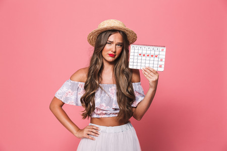 Portrait of caucasian woman 20s wearing straw hat holding period calendar isolated over pink background in studio