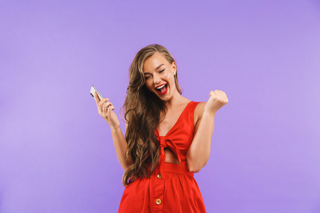 Image closeup of joyful young woman 20s wearing red dress screaming and rejoicing while holding mobile phone standing isolated over violet background