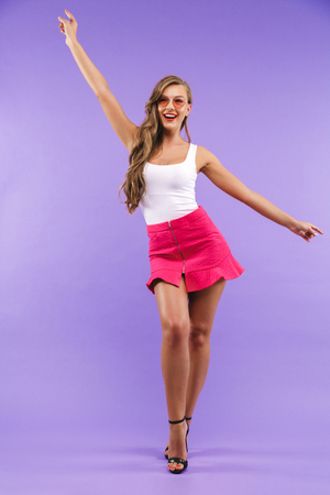 Full length portrait of happy brunette woman 20s in summer clothes and sunglasses having fun and dancing with arms standing isolated over violet background Stock Photo