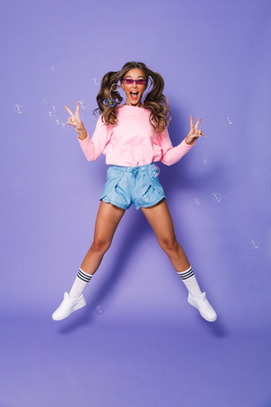 Full length portrait of excited joyous girl with two ponytails in sweatshirt smiling and jumping isolated over violet background in studio