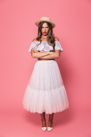 Full length portrait of upset offended woman 20s wearing straw hat and fluffy skirt pouting in resentment with arms crossed isolated over pink background Stock Photo
